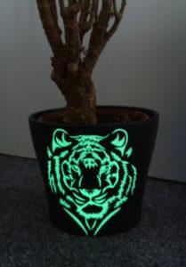 Blumentopf beklebt mit lumentics-Leuchtaufklebern in Form eines Tigerkopfes im Hellen