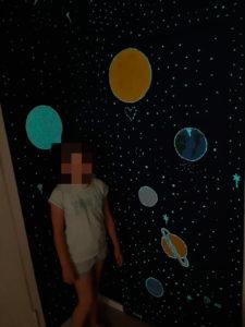 Wandmalerei des Sonnensystem mit grünblauer lumentics-Leuchtfarbe bei Nacht